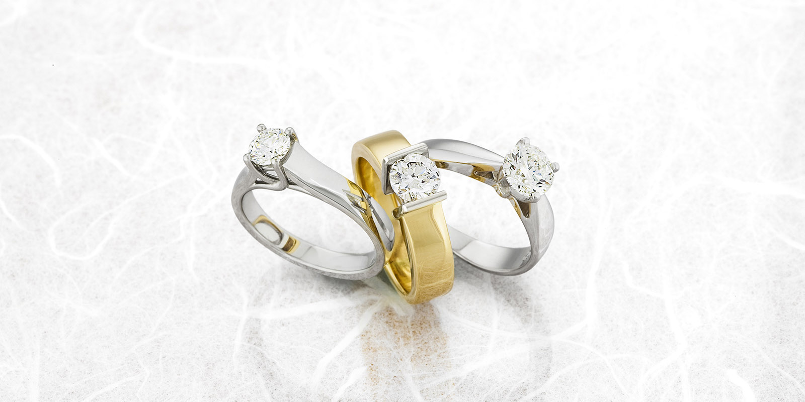 Three Engagement Rings on Reflective Surface