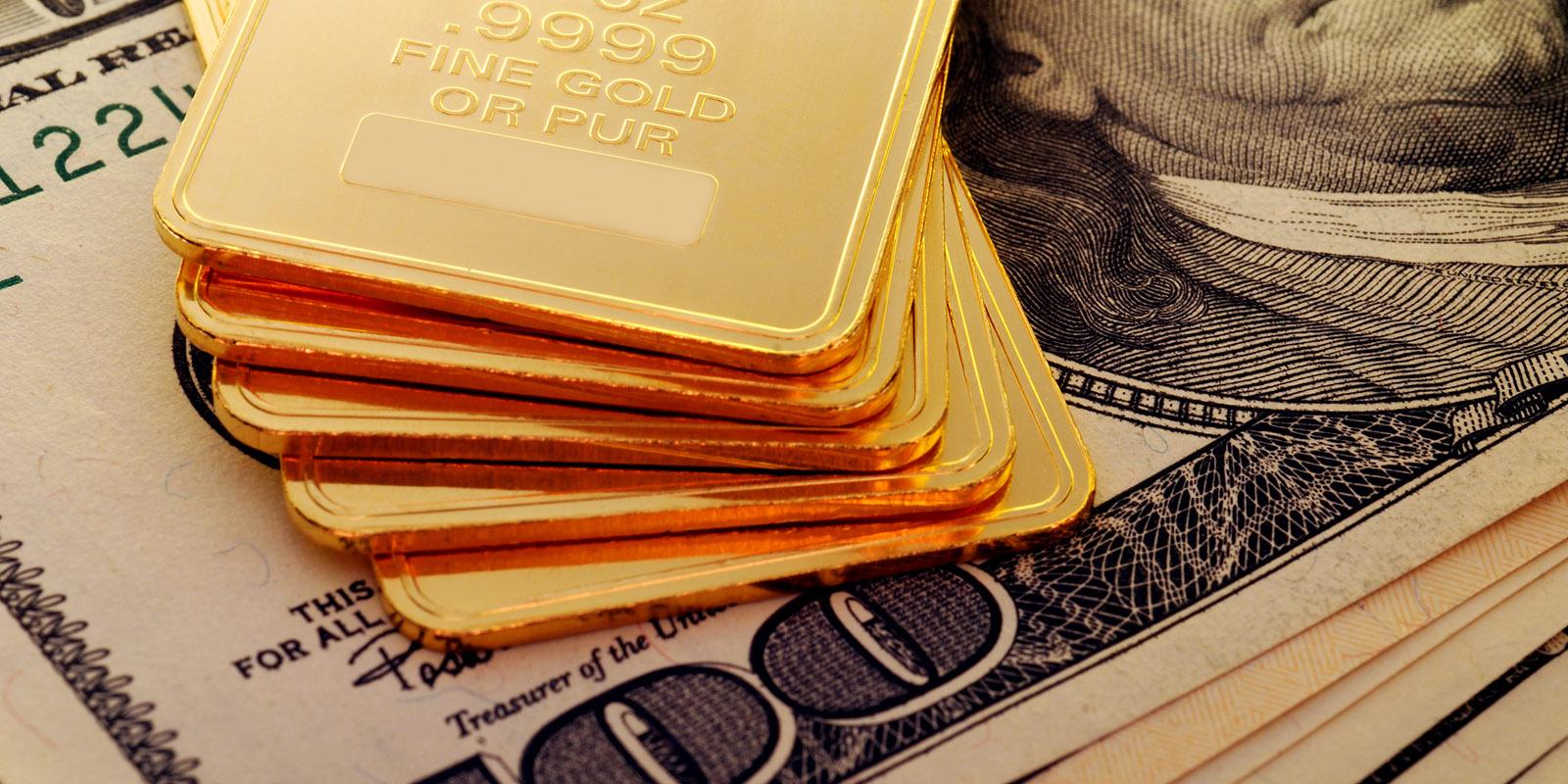 gold ingots displayed on top of 100 dollar bills