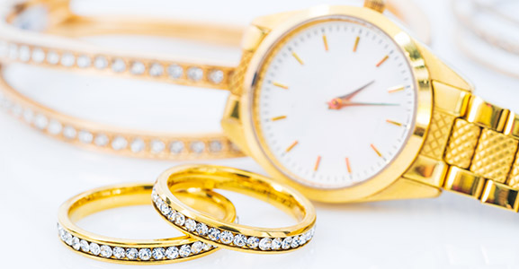 Luxury gold ring and lady gold watch on white